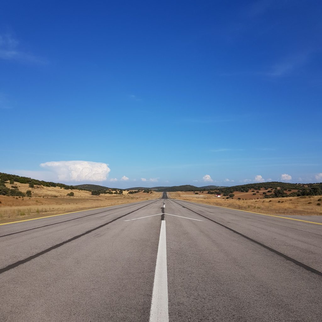 gray asphalt road under blue sky during daytime