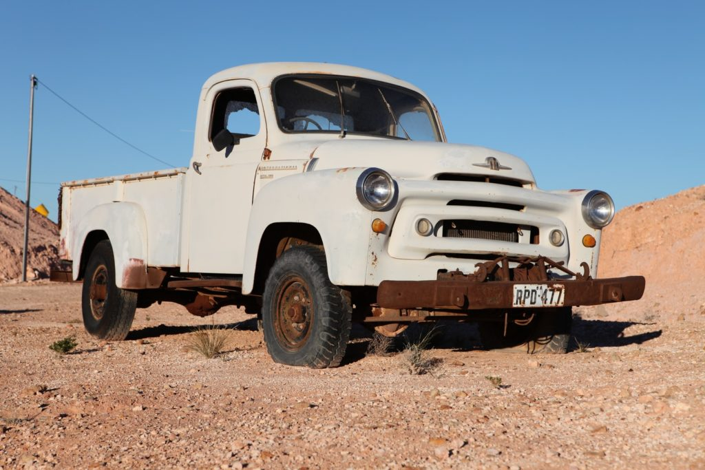 white single cab pickup truck on brown dirt ground during daytime
