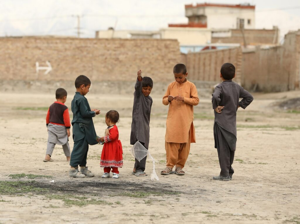 children in red and gray shirts standing on gray sand during daytime