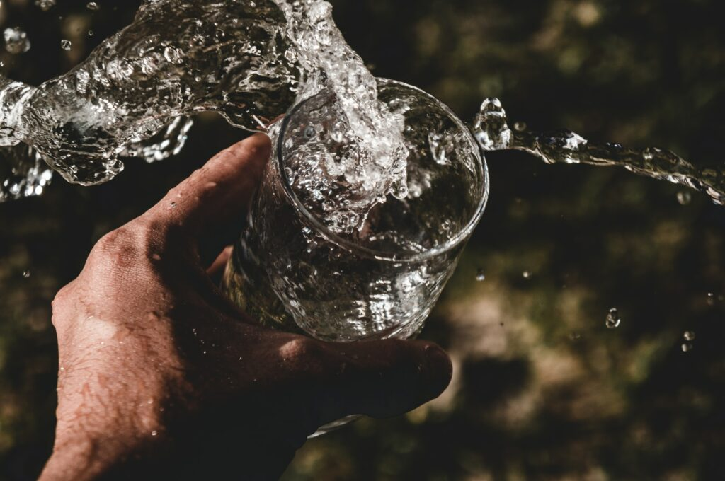 person holding drinking glass filled with water